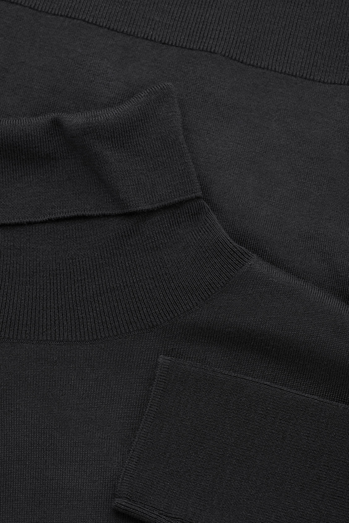 Side image of Cos roll-neck merino jumper in black