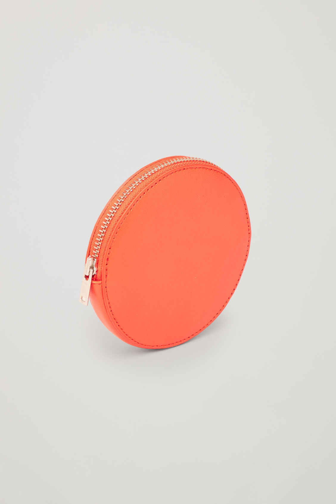Side image of Cos round leather purse in orange