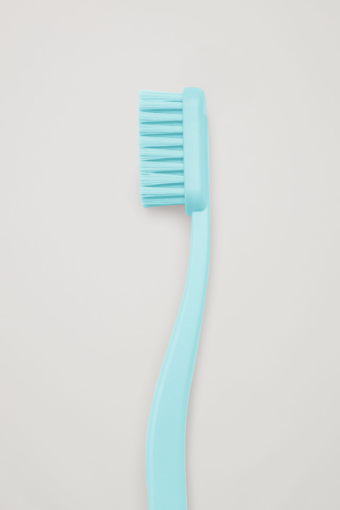 Side image of Cos hay tann toothbrush in blue