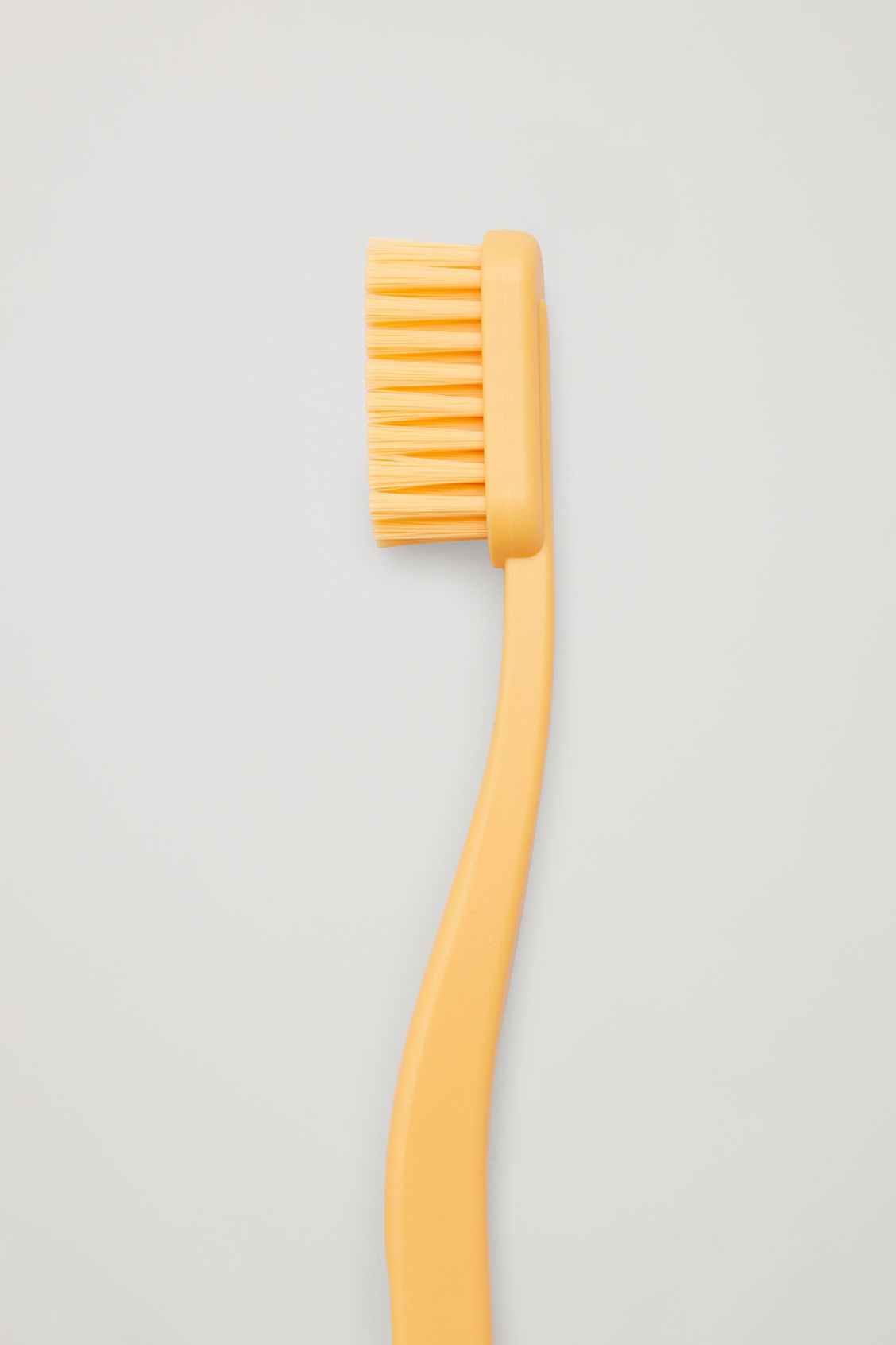 Side image of Cos hay tann toothbrush in yellow