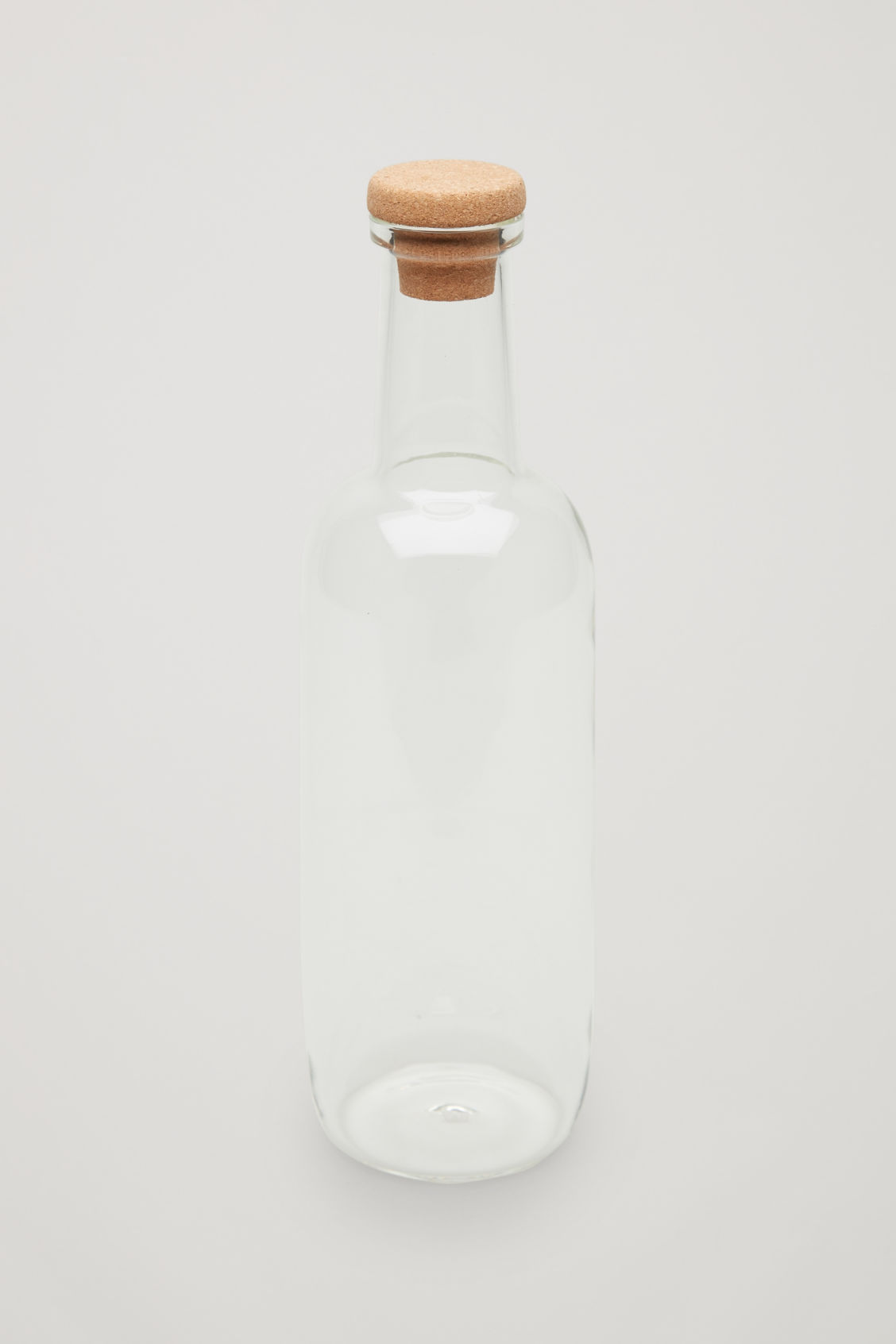 Side image of Cos hay small glass bottle in white