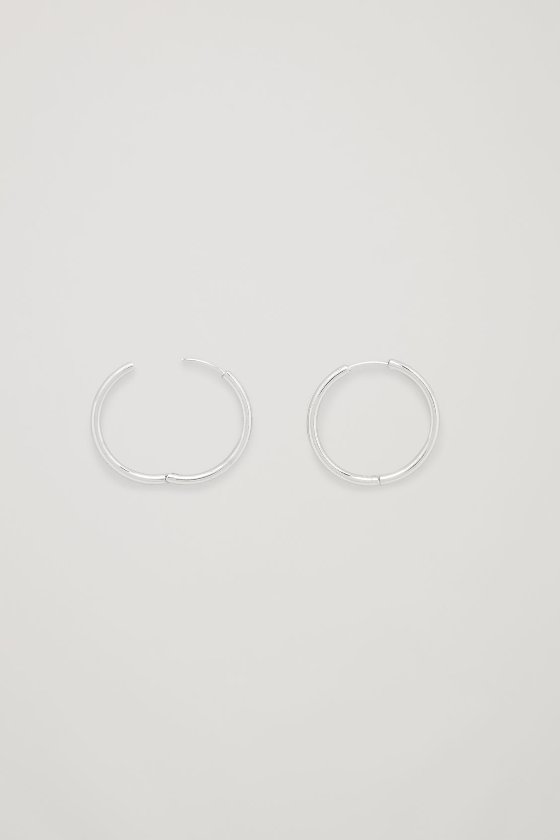 Side image of Cos mid-hoop earrings in silver