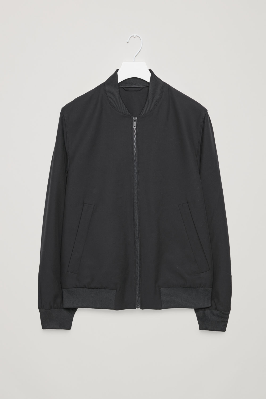 Front image of Cos bomber jacket with zipped pockets  in black