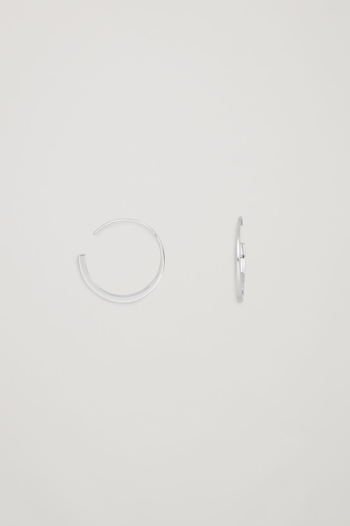 Side image of Cos changing profile hoop earrings in silver