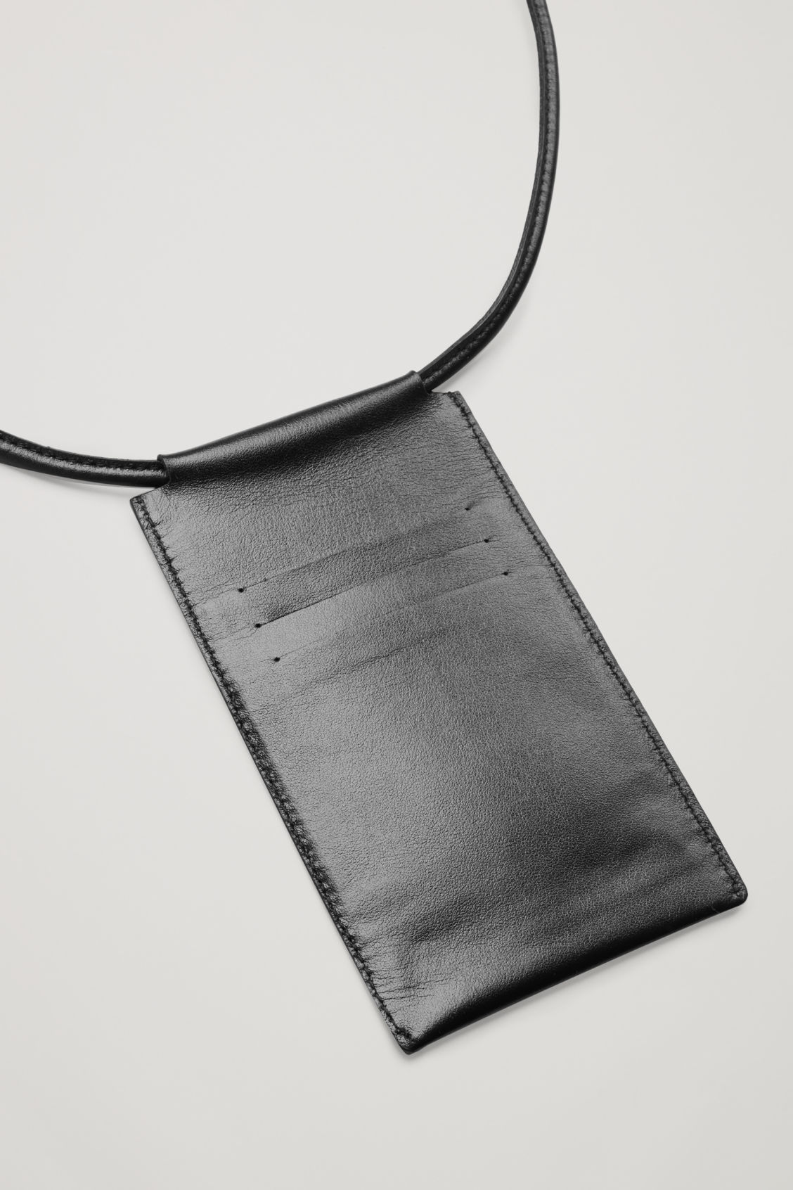Side image of Cos leather phone pouch in black