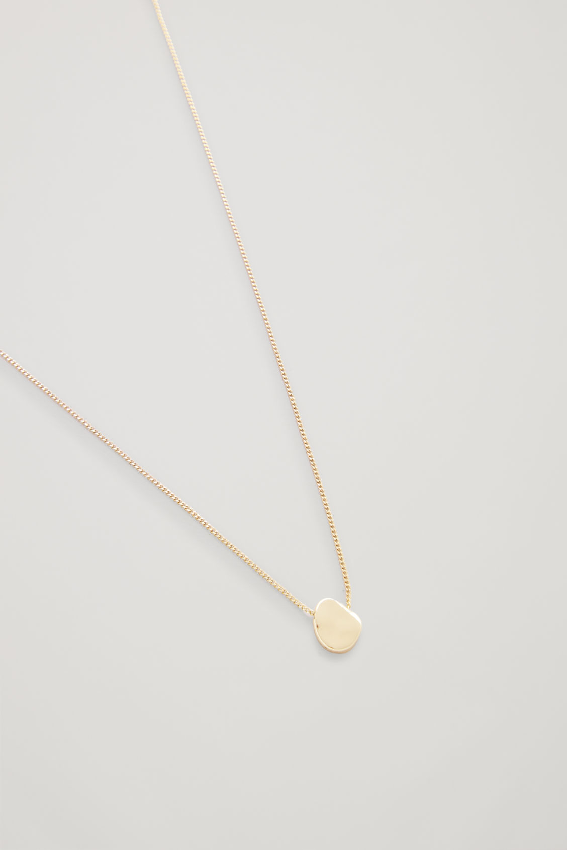 Side image of Cos short necklace with uneven disc  in gold