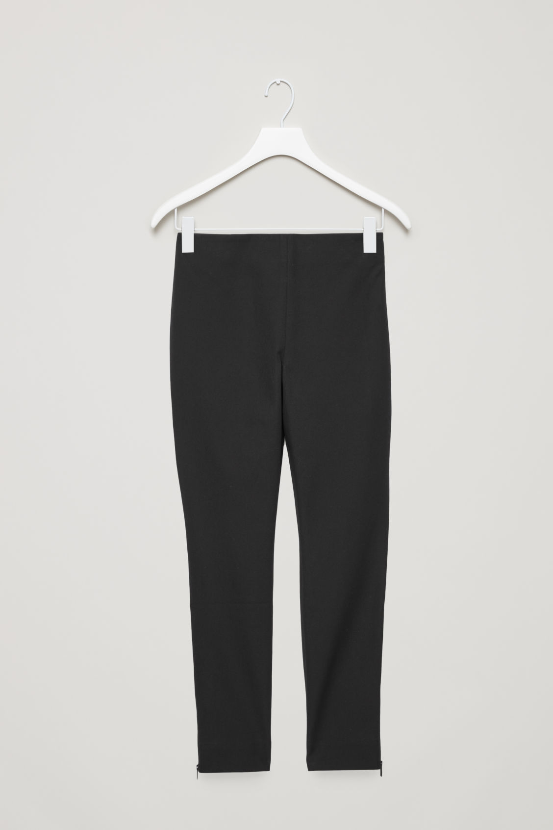 Front image of Cos trousers with ankle zips  in black
