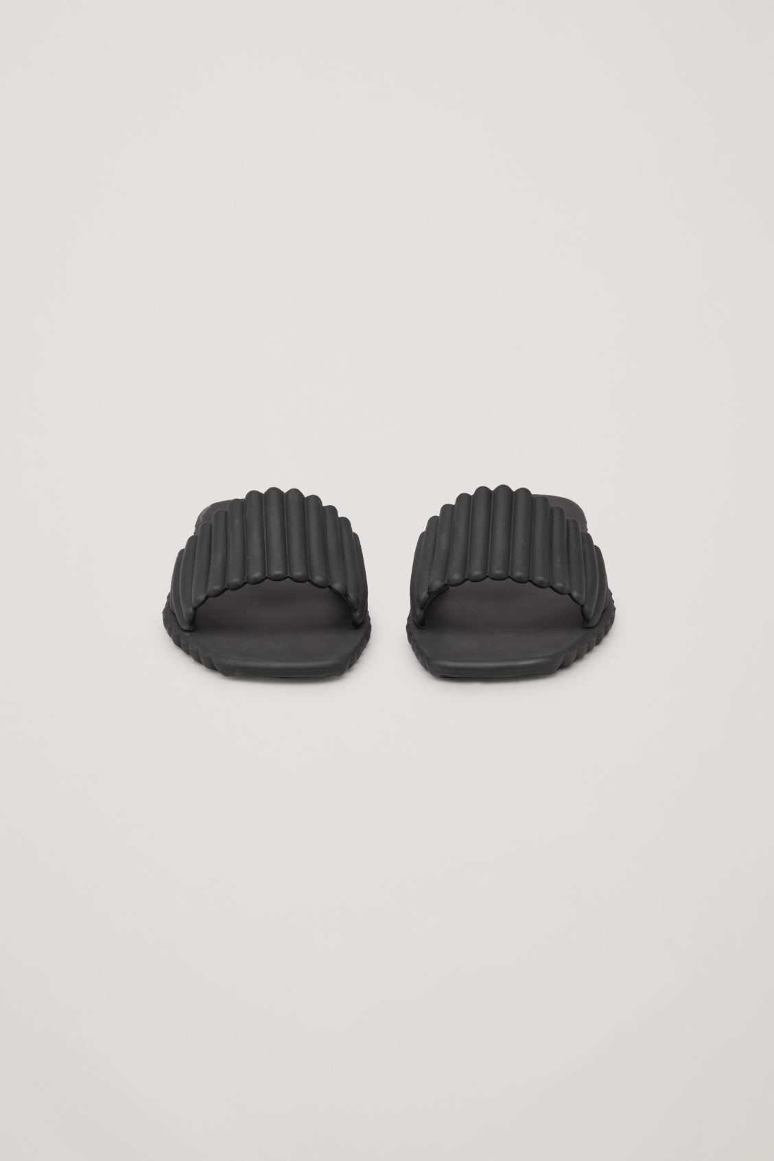 Side image of Cos scalloped rubber sliders in black
