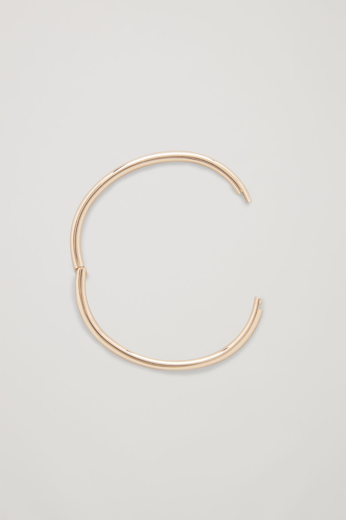 Side image of Cos circle-cut metal bangle in gold