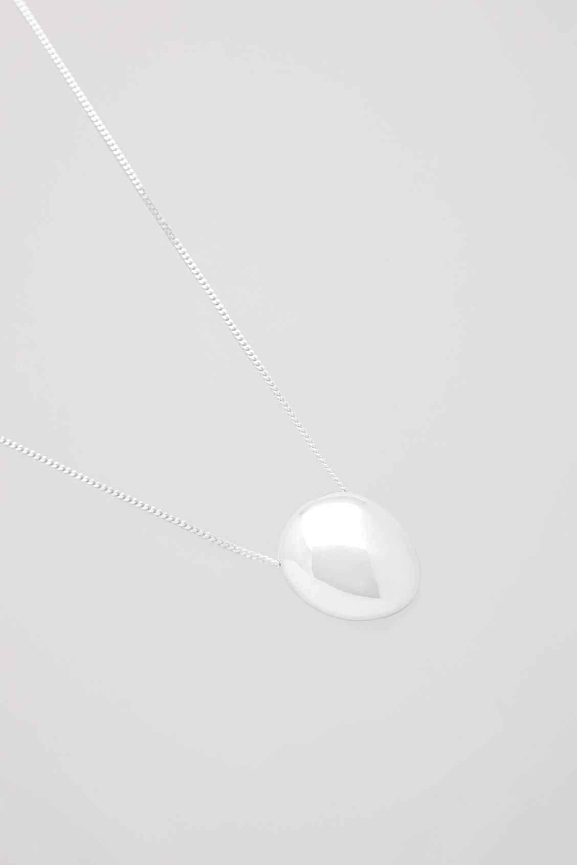 Side image of Cos abstract pendant necklace in silver