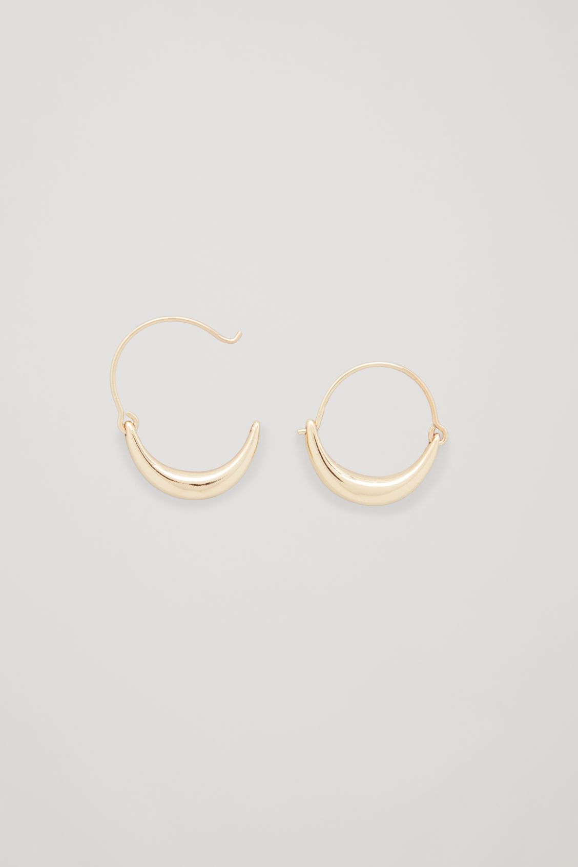 Side image of Cos abstract hoop earrings in gold