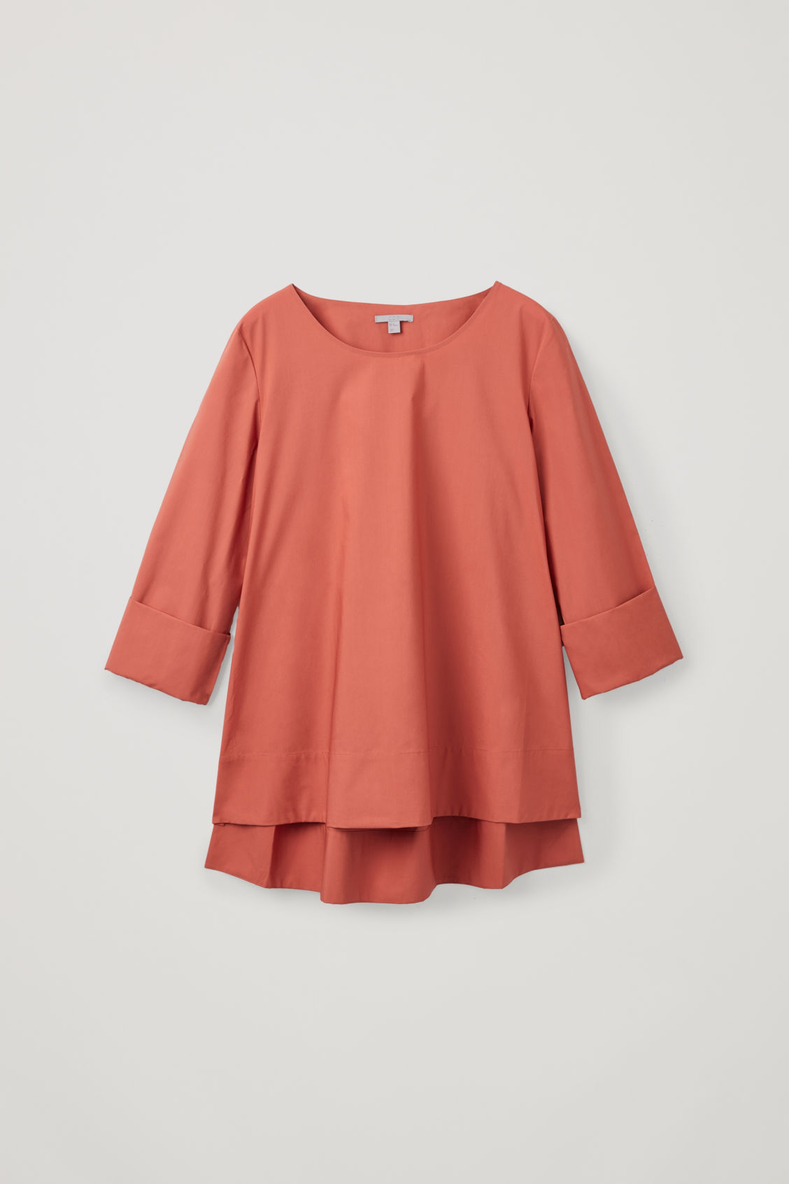 Front image of Cos a-line top with folded cuffs in orange