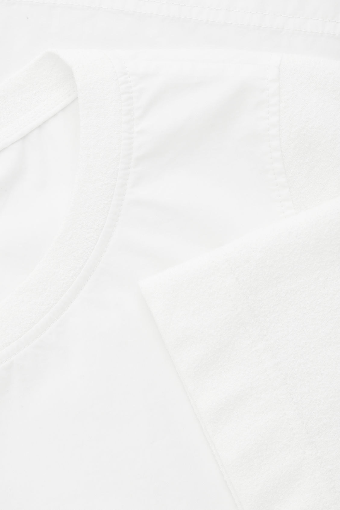 Side image of Cos top with textured sleeves in white