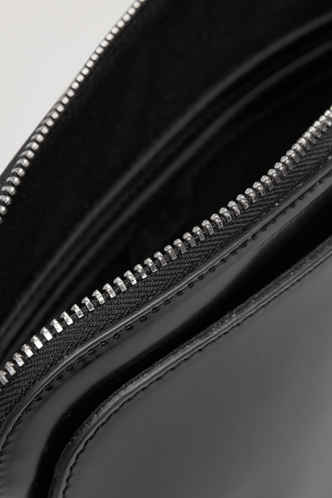 Side image of Cos polished leather crossbody bag in black