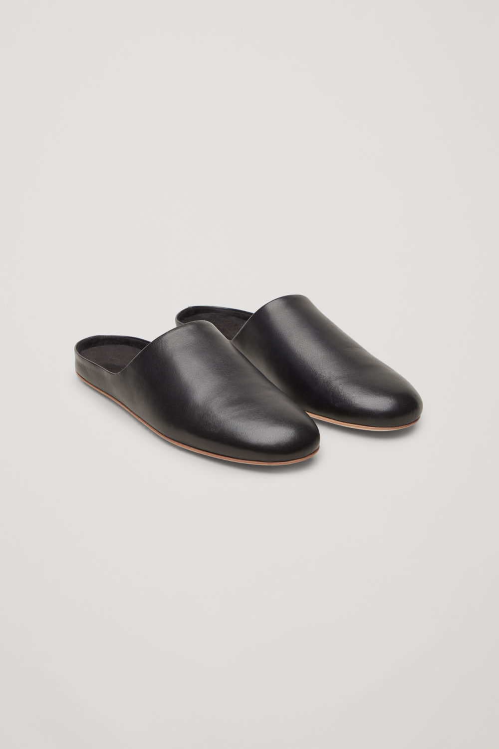 Front image of Cos leather slippers in black