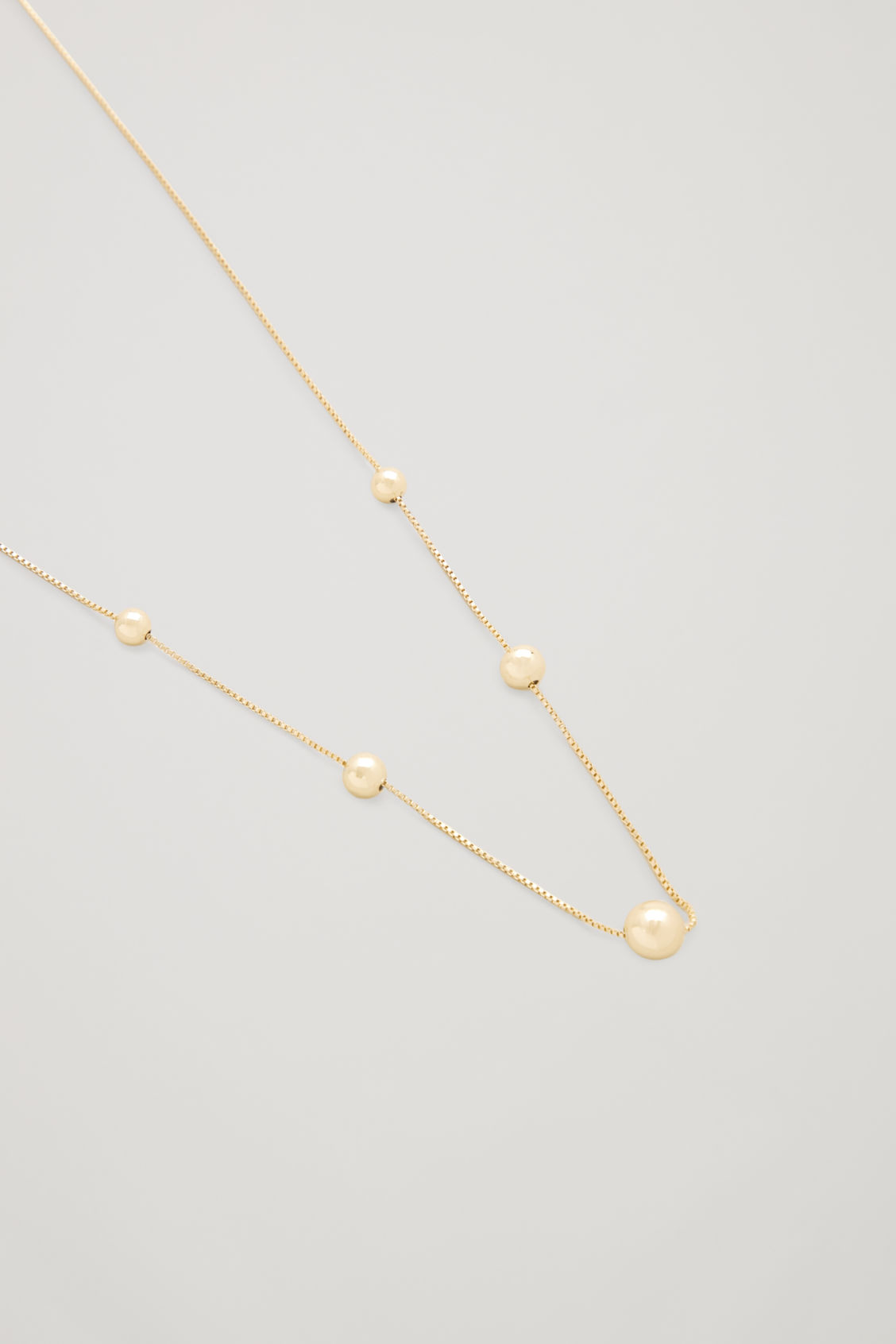 Side image of Cos beaded short chain necklace in gold