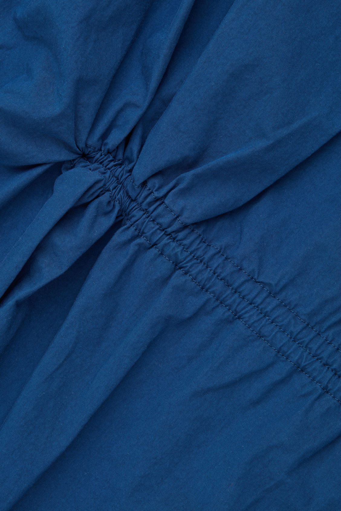 Side image of Cos long jacket with gathered back in blue