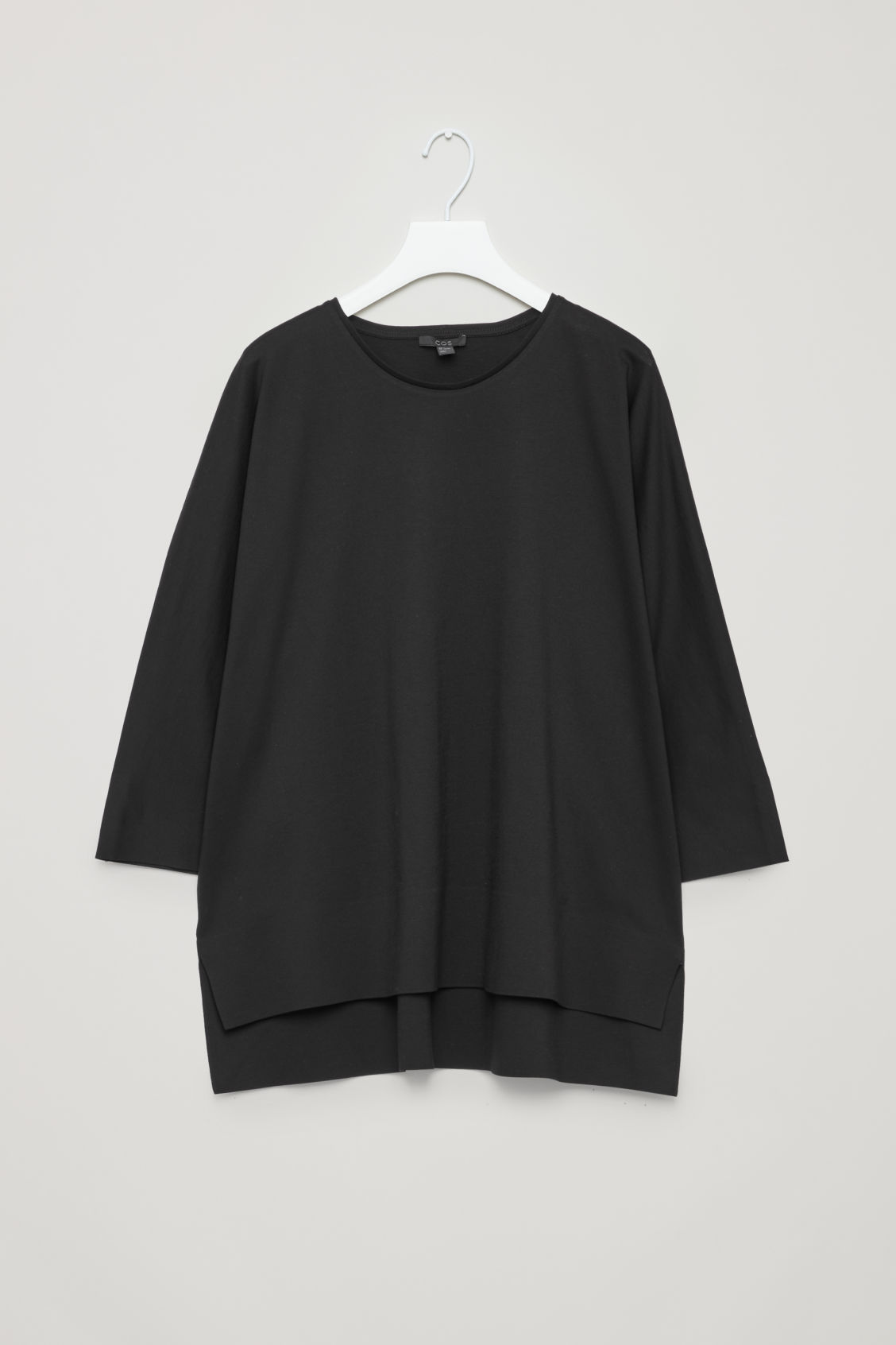Front image of Cos jersey top with bound details in black