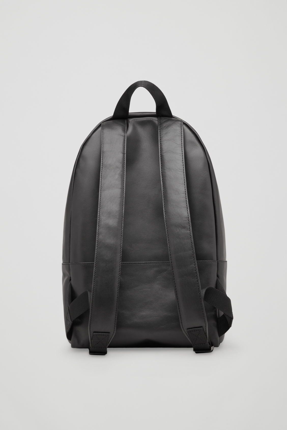 Side image of Cos leather backpack in black