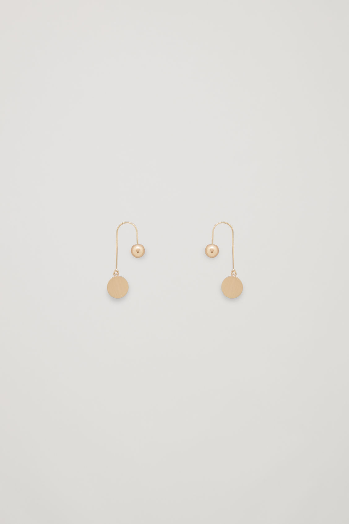 Front image of Cos ball and disc drop earrings in gold