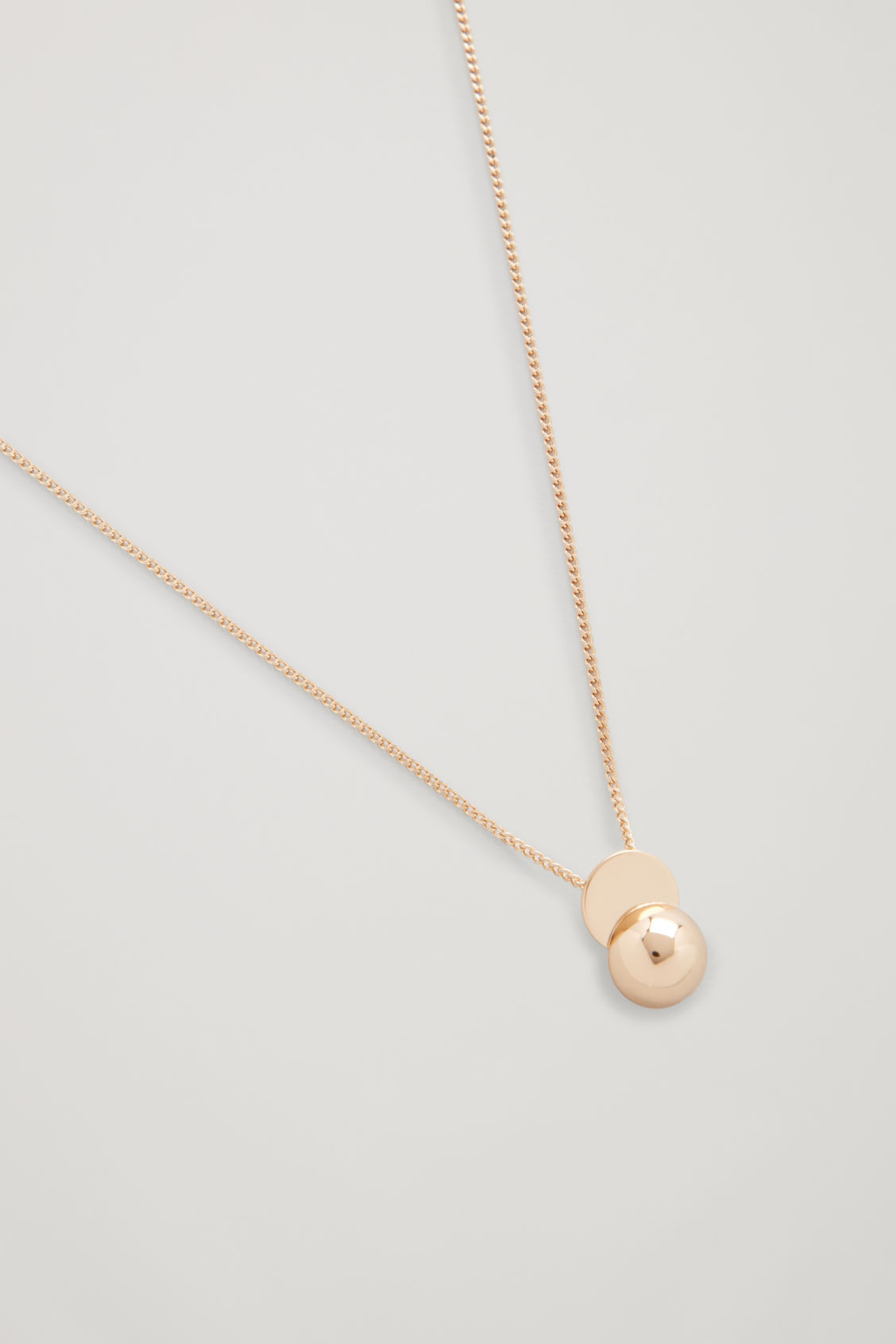 Side image of Cos semi-circle pendant necklace in gold