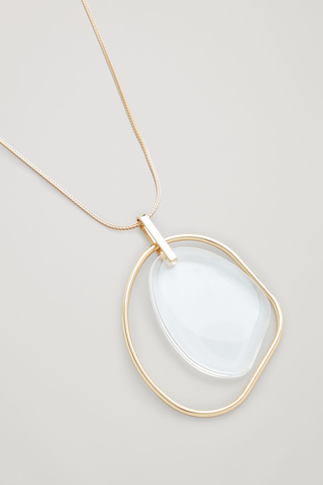 Side image of Cos long glass pendant necklace  in gold