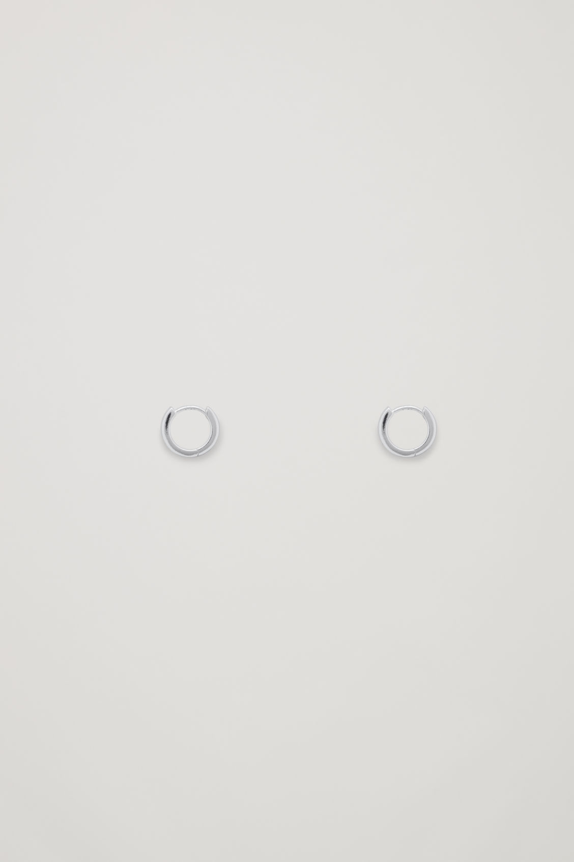 Front image of Cos micro hoop earrings in silver
