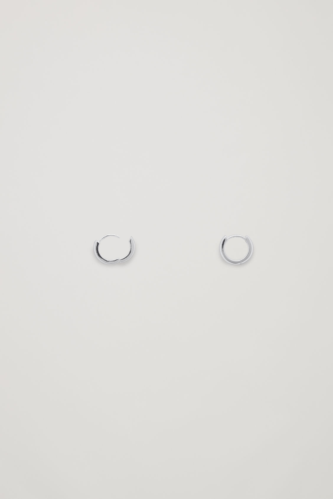 Side image of Cos micro hoop earrings in silver