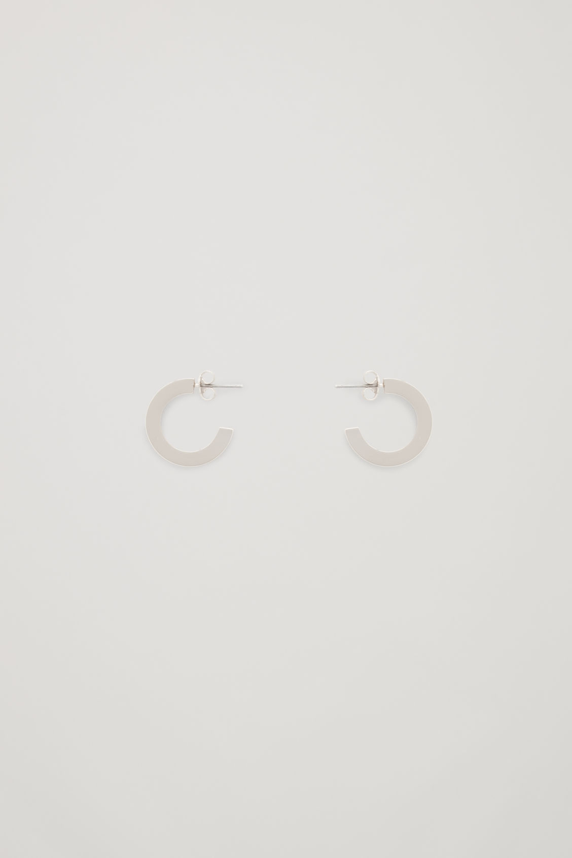 Front image of Cos mismatched hoop earrings in silver