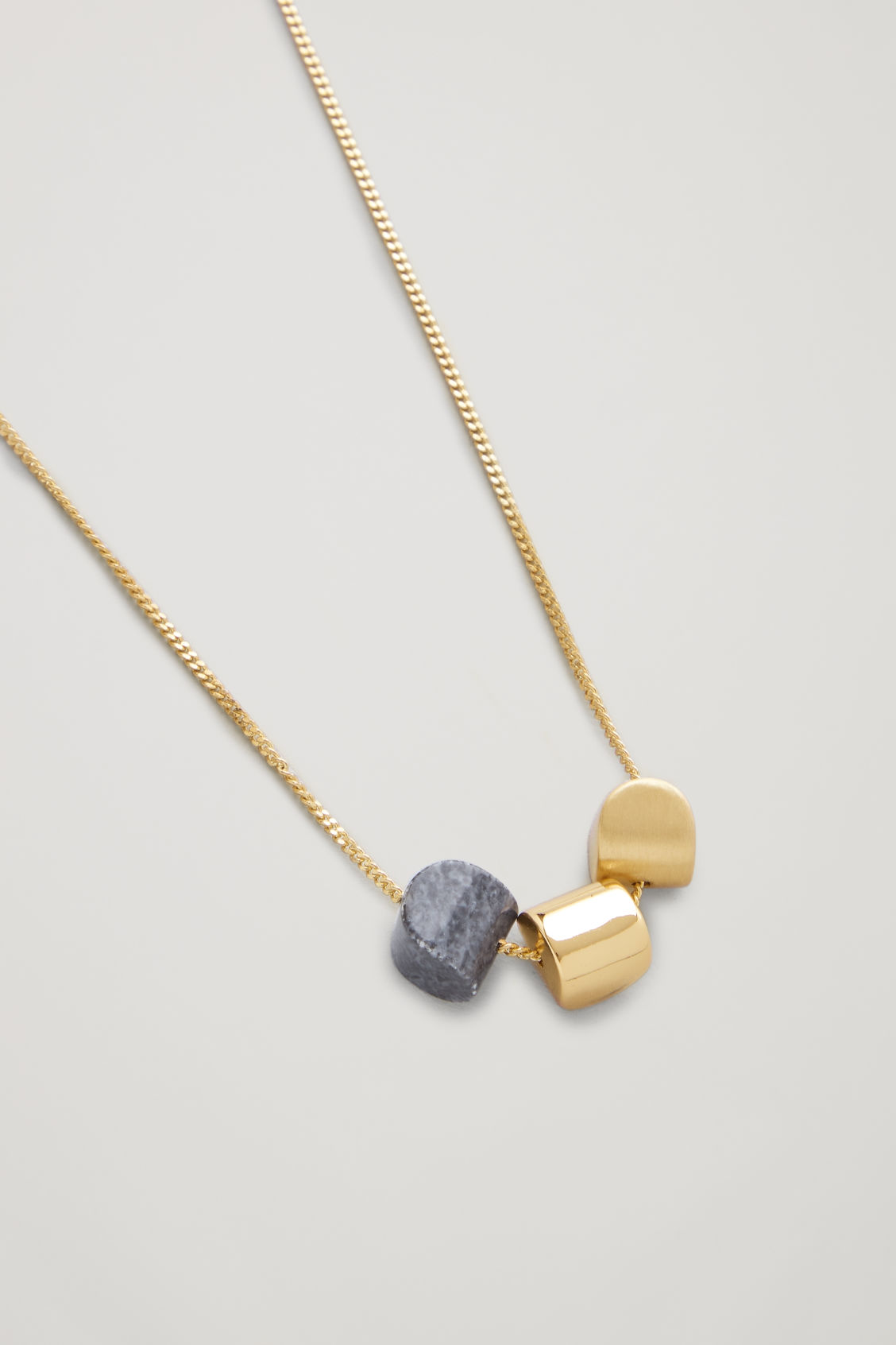 Side image of Cos mixed pendant short necklace in gold