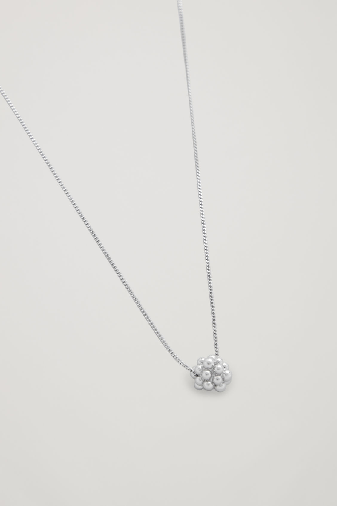 Side image of Cos cluster shape short necklace in silver