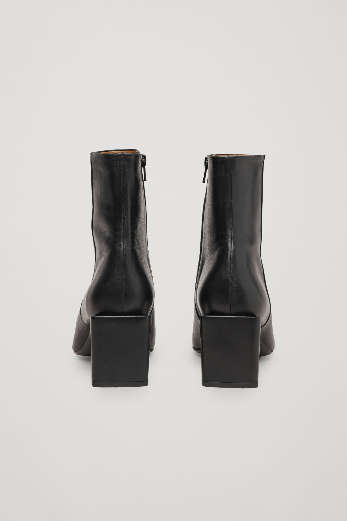 Side image of Cos sculptural leather ankle boots in black