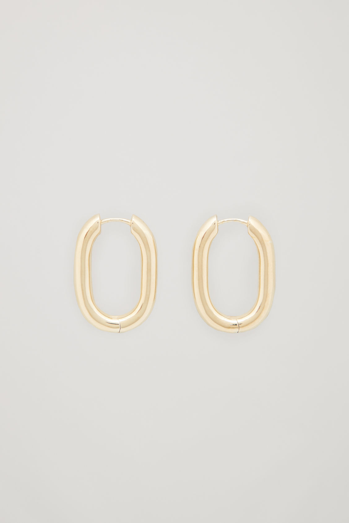 Front image of Cos oval gold-plated hoop earrings in gold