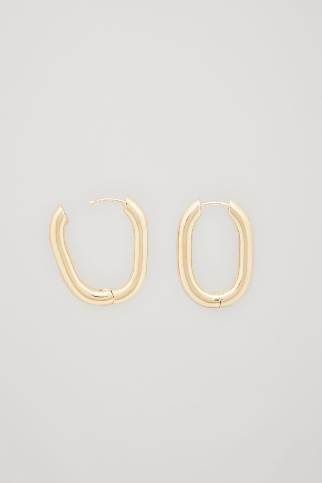 Side image of Cos oval gold-plated hoop earrings in gold