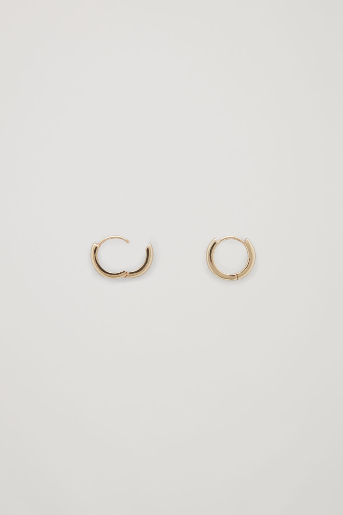 Side image of Cos gold-plated micro hoop earrings in gold