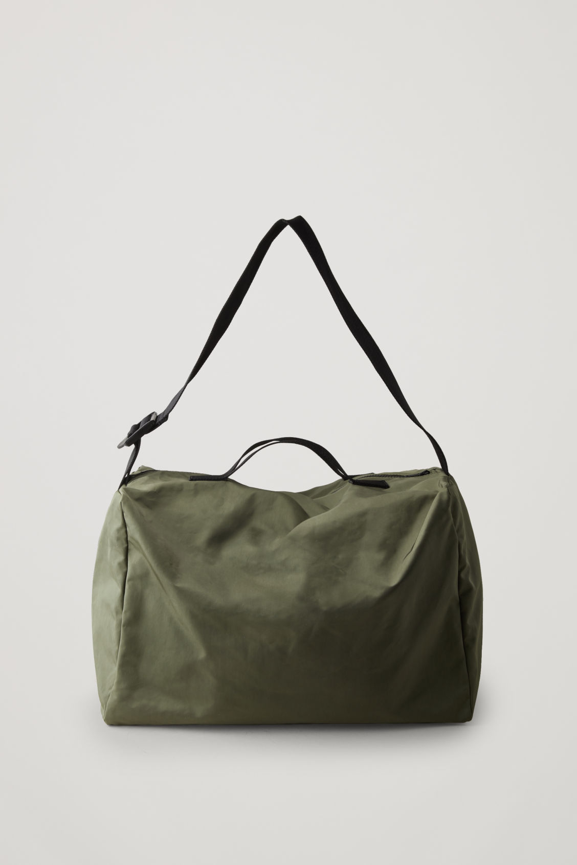 Front image of Cos collapsed technical holdall in green