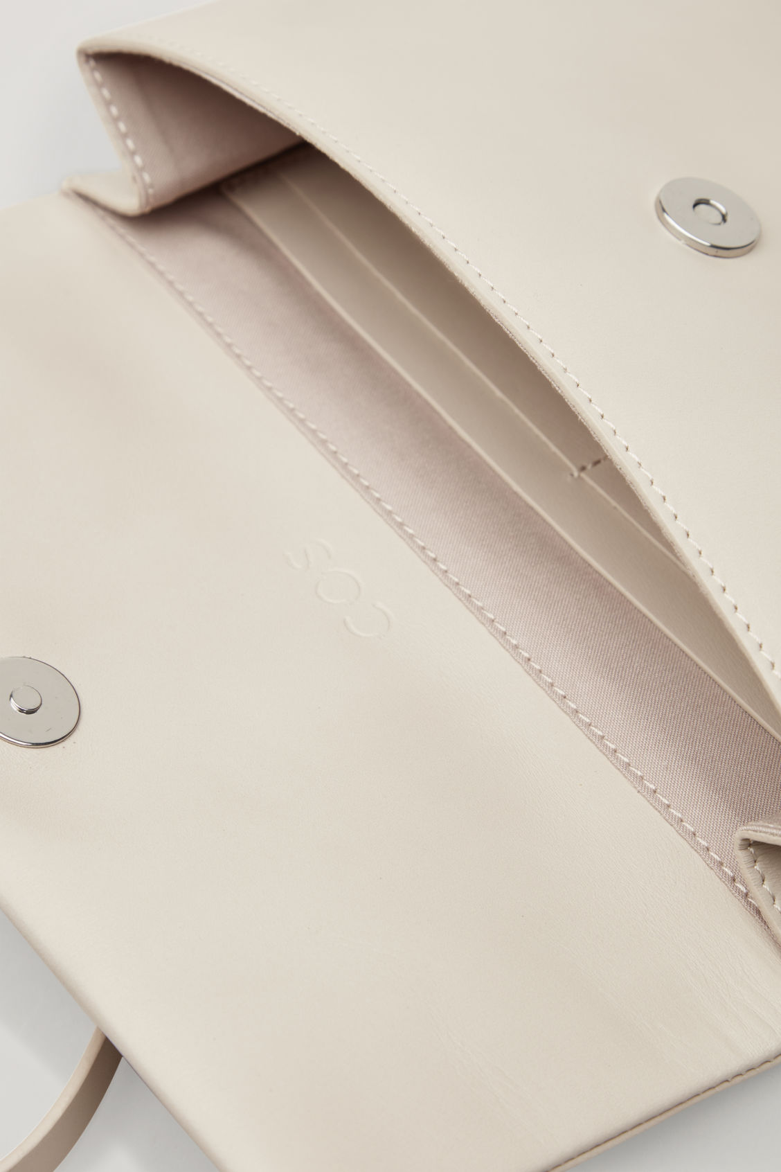 Side image of Cos leather clutch with card slots in beige