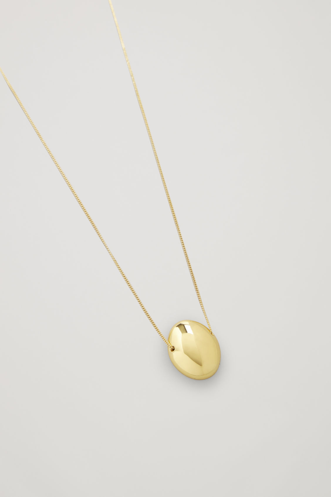 Side image of Cos curved gold-plated pendant necklace in gold