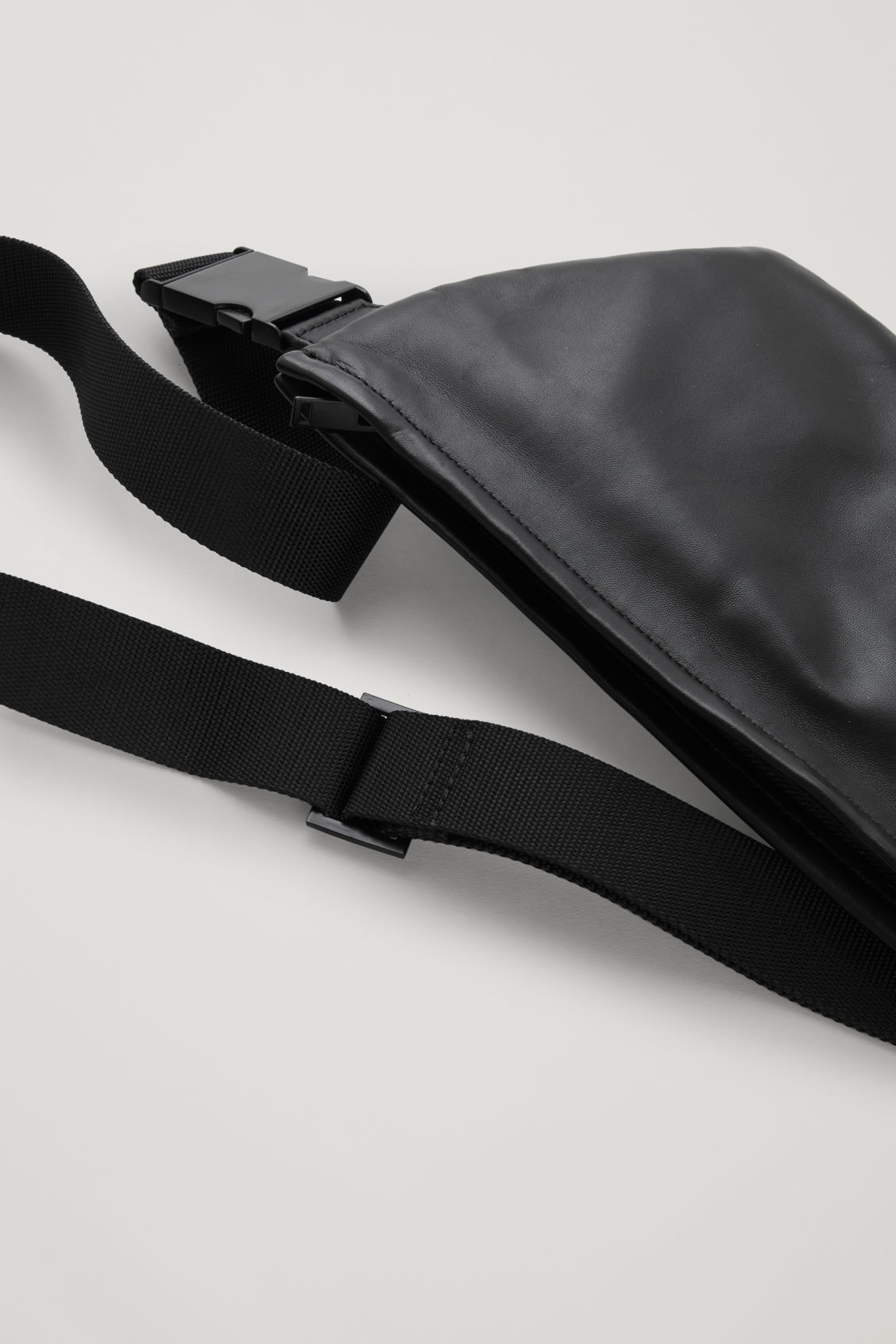 Side image of Cos leather zip-up belt bag in black