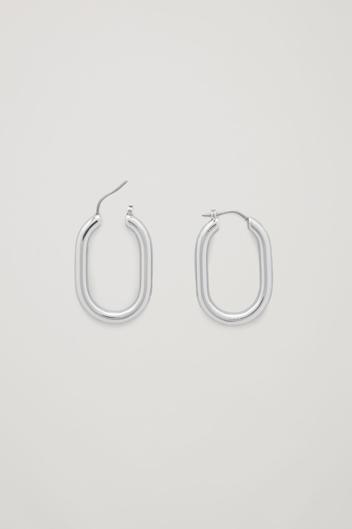 Side image of Cos oval hoop earrings in silver