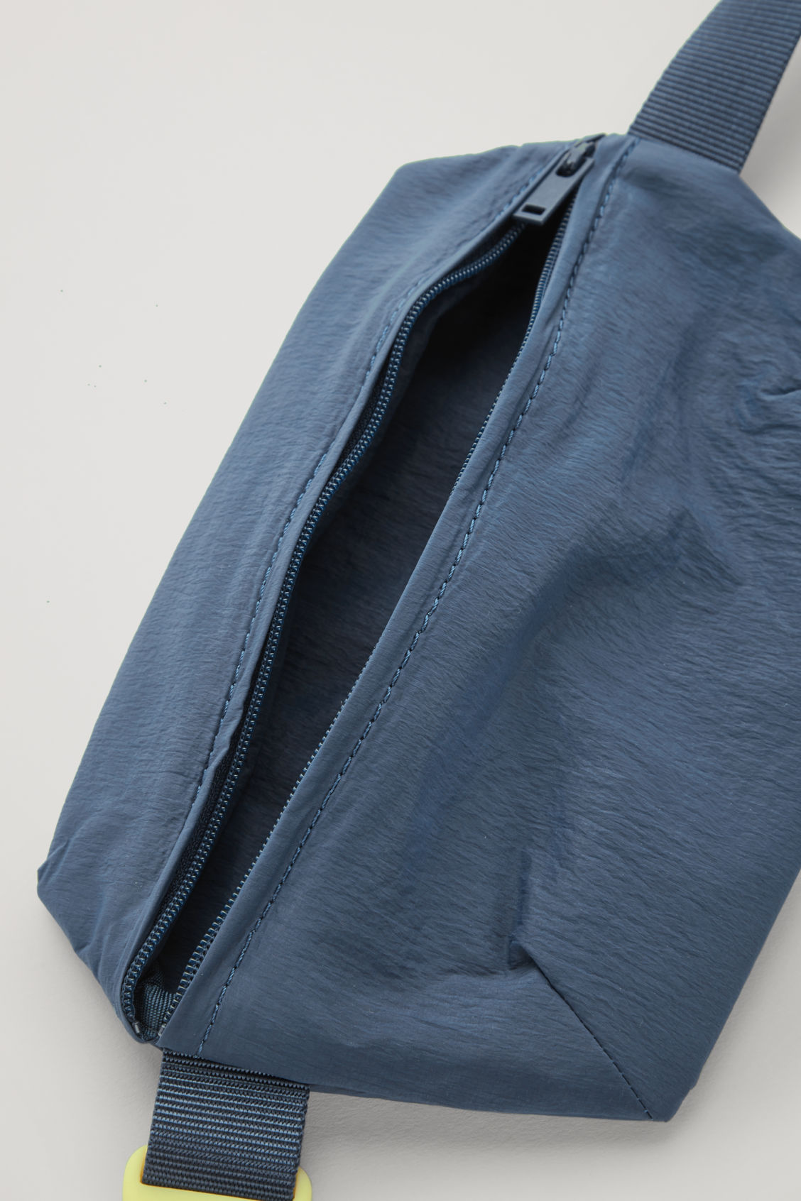 Side image of Cos zip-pocket belt bag in blue