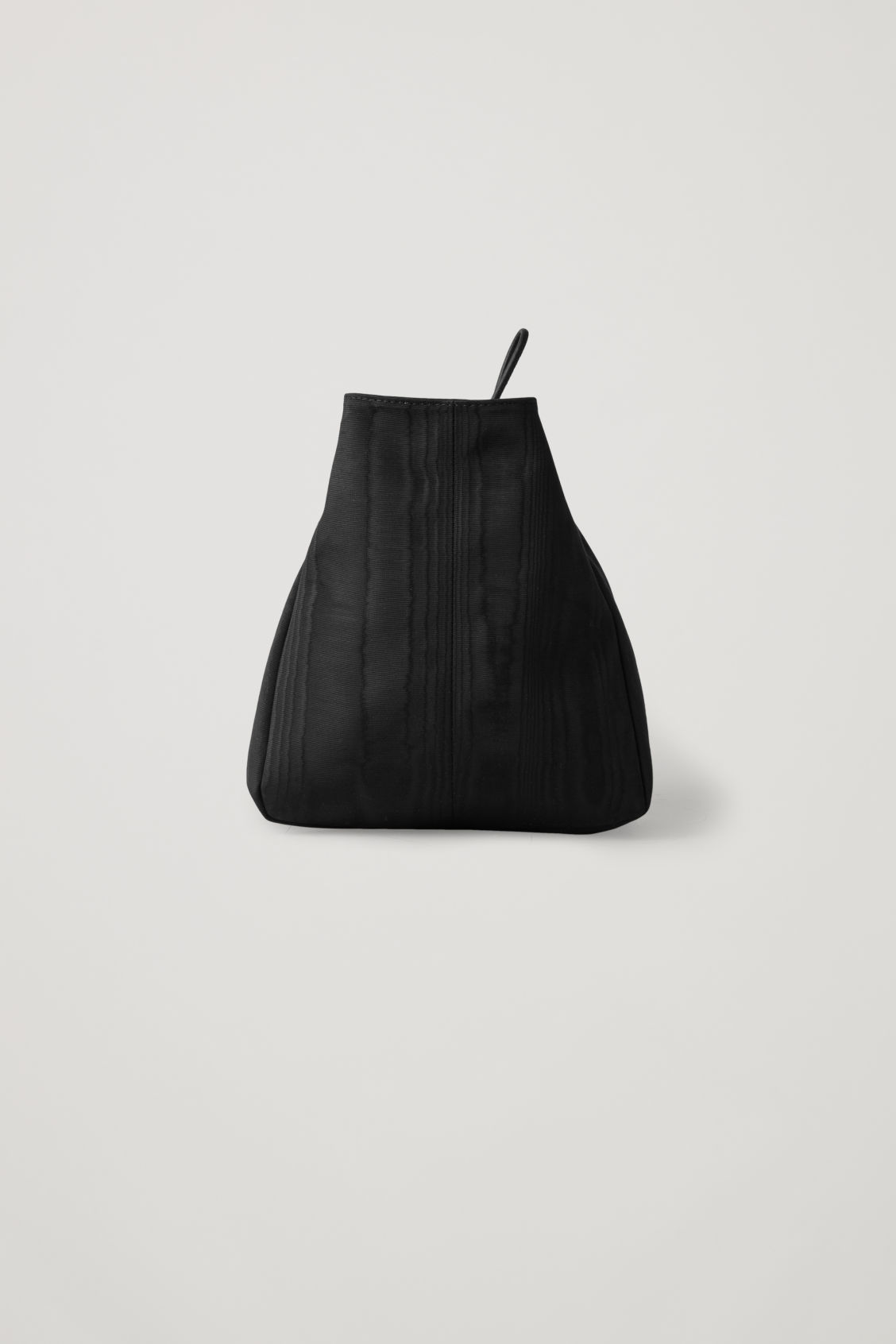 Side image of Cos moire-pattern wrist bag in black