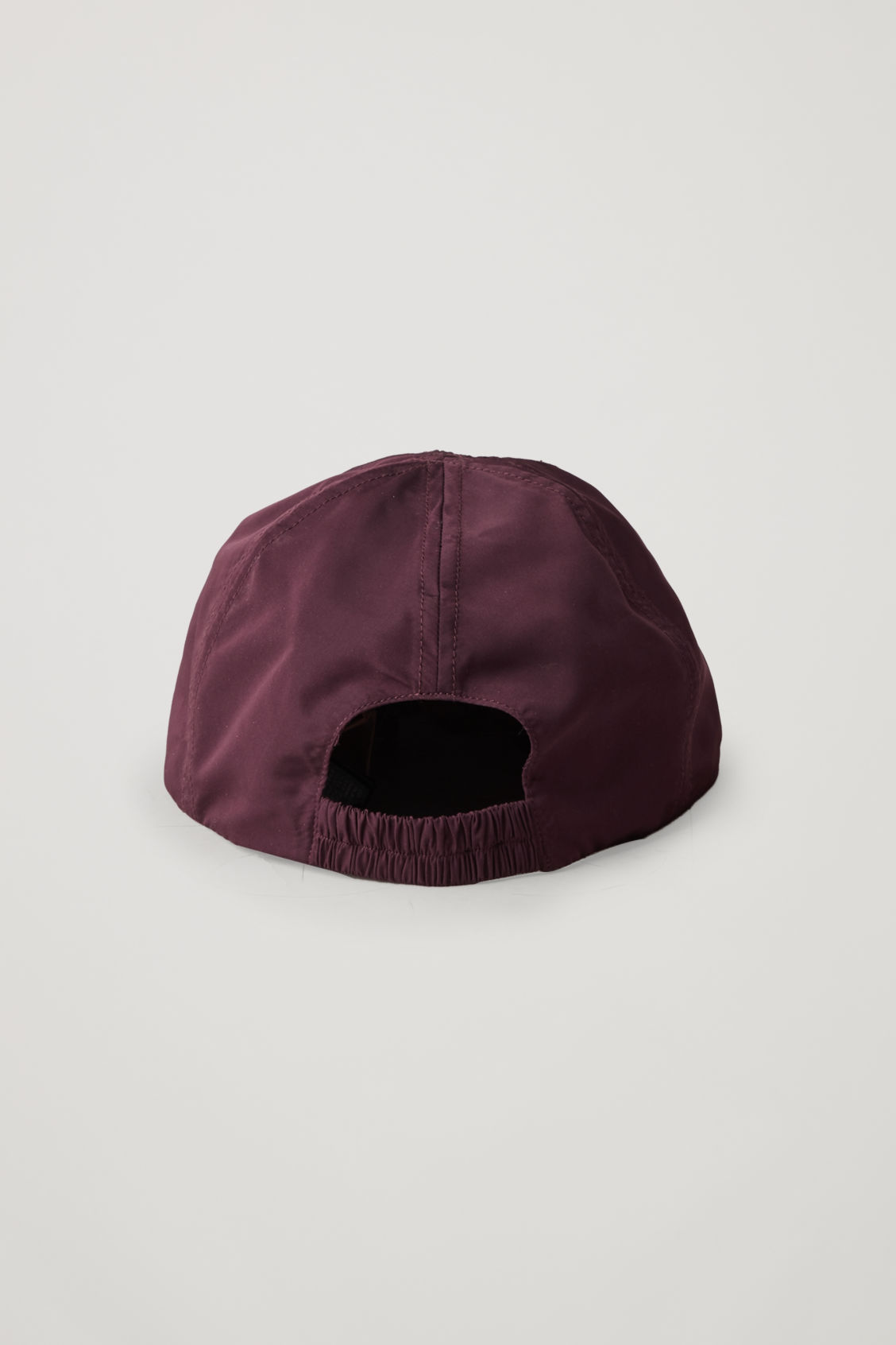Side image of Cos technical baseball cap in burgundy