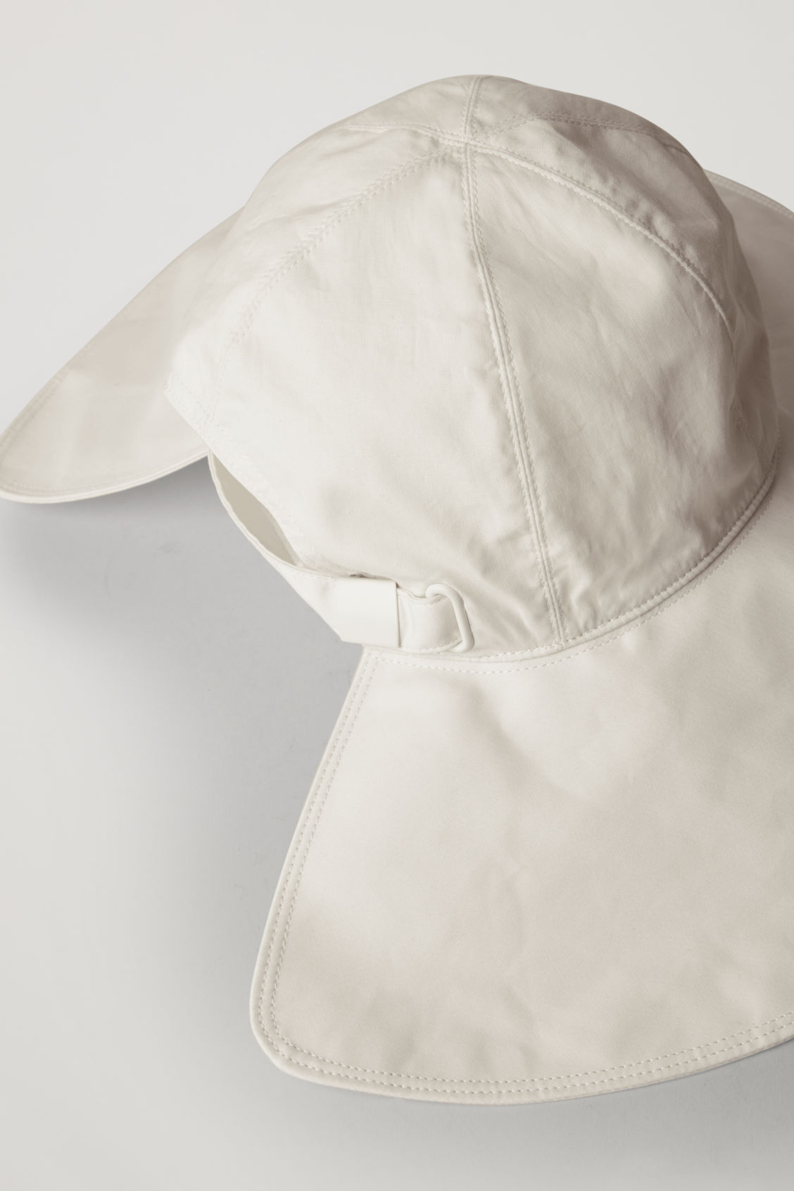 Side image of Cos wide-brim hat with open back in cream