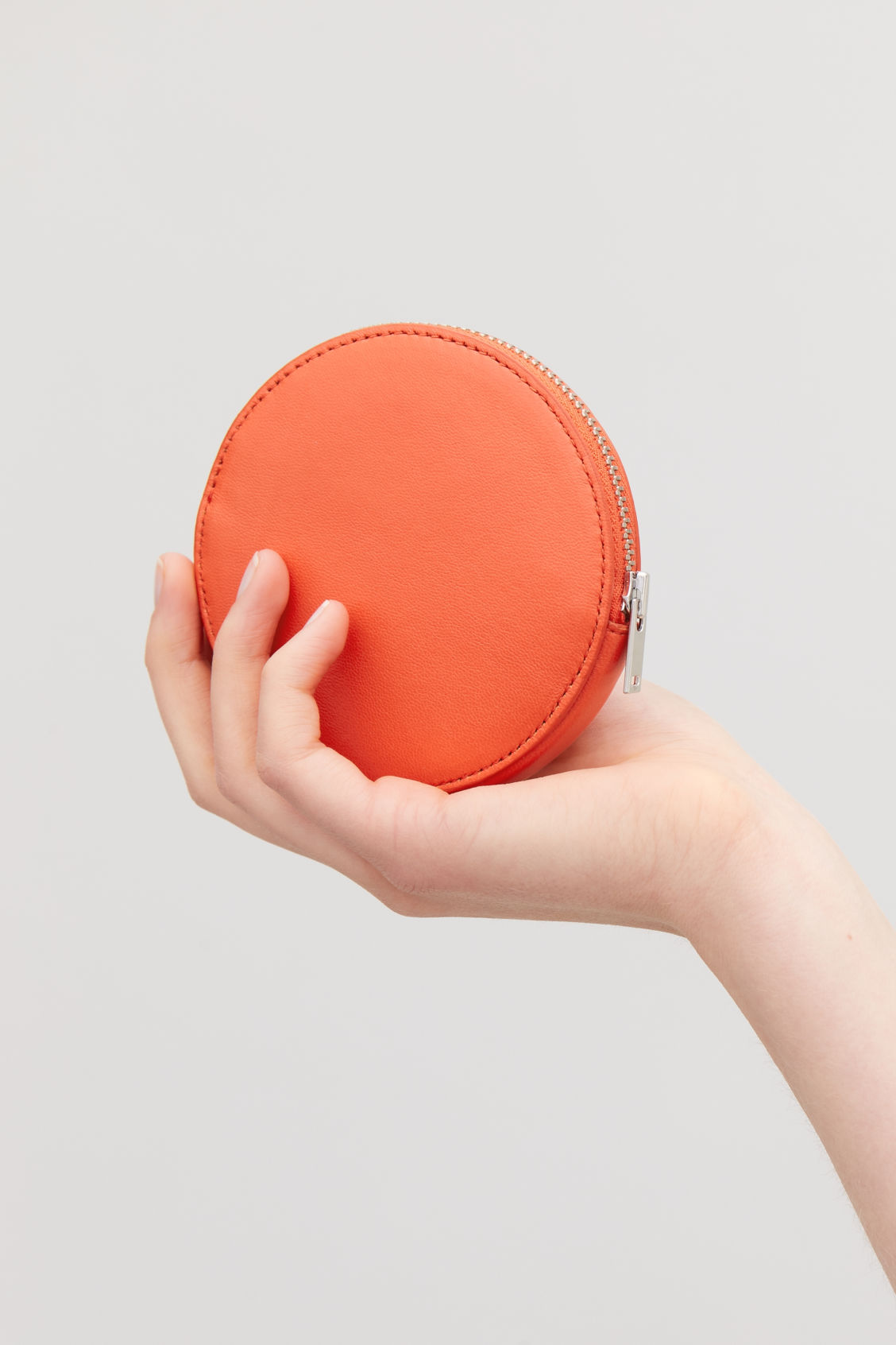 Detailed image of Cos round leather purse in orange
