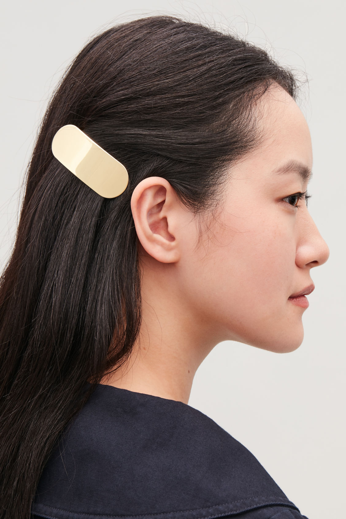 Detailed image of Cos oval-shaped hair clip in gold