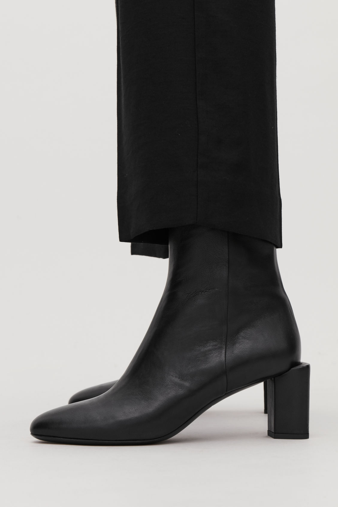 Detailed image of Cos sculptural leather ankle boots in black