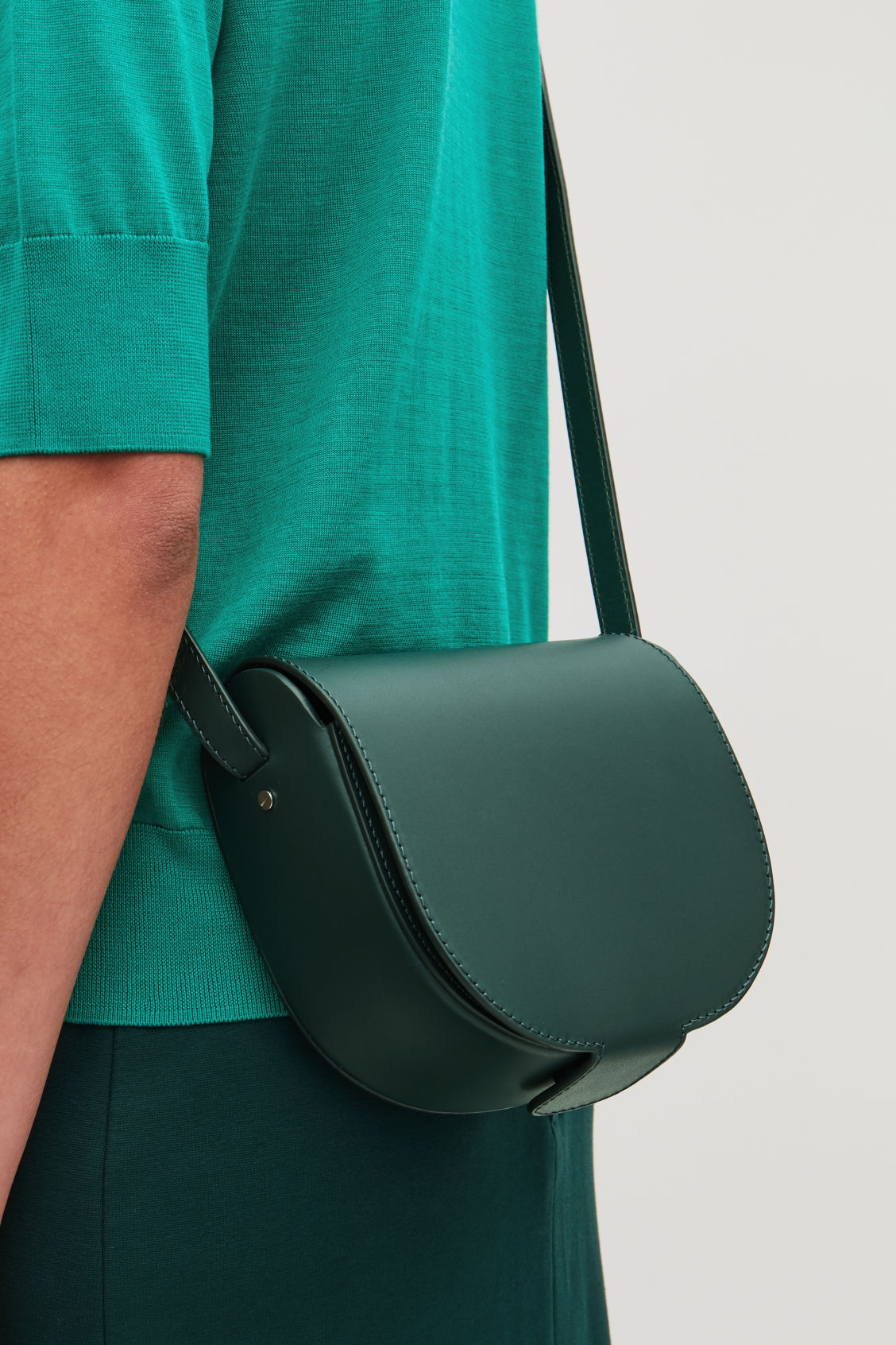 Detailed image of Cos small leather saddle bag in green