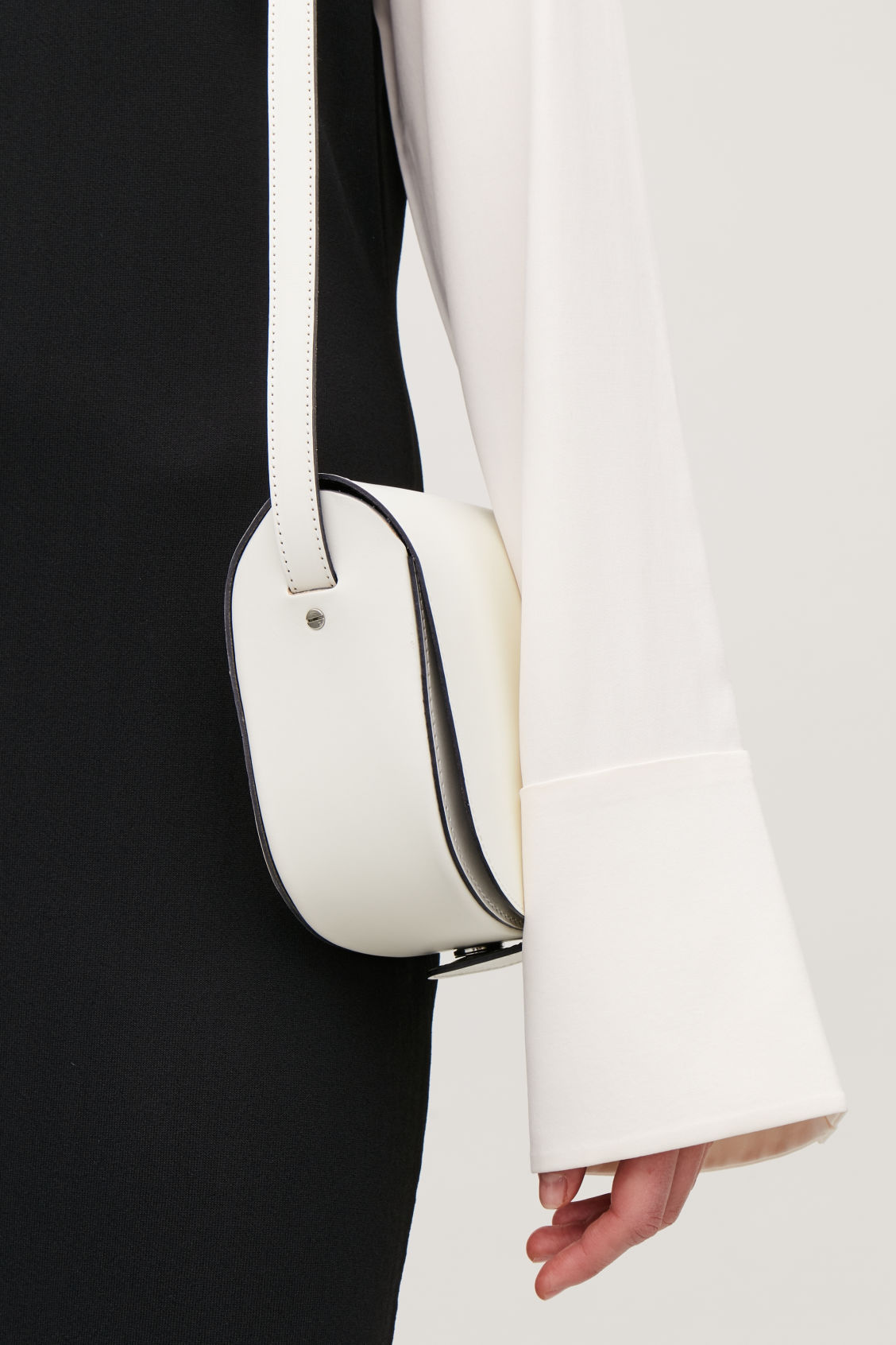 Detailed image of Cos small leather saddle bag in white