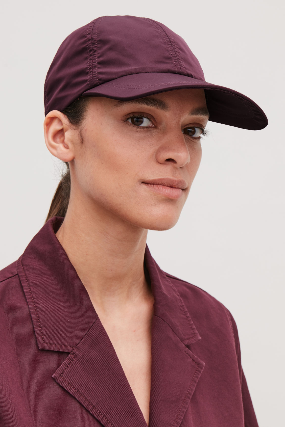 Detailed image of Cos technical baseball cap in burgundy
